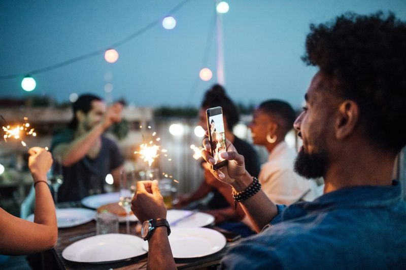 Person taking a photo at a party with their own phone