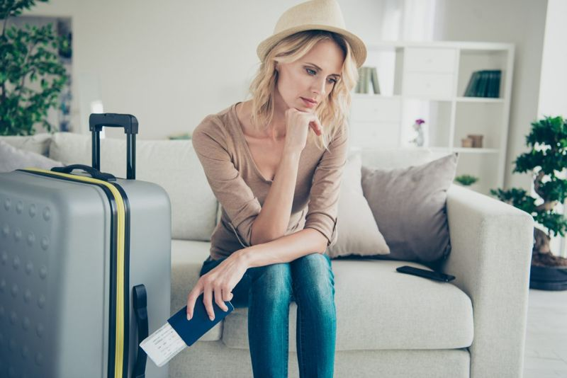 Sad lady sitting down with a suitcase