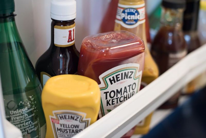Ketchup and mustard sitting in a fridge