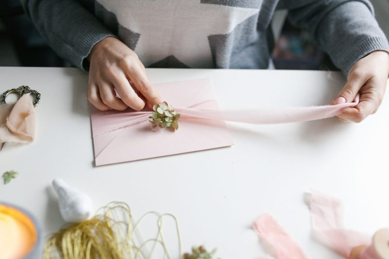 Girl wrapping wedding invitation using a ribbon