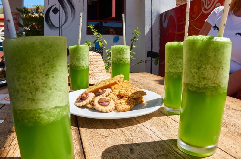 Smoothies on a table with a plate of cookies in the middle