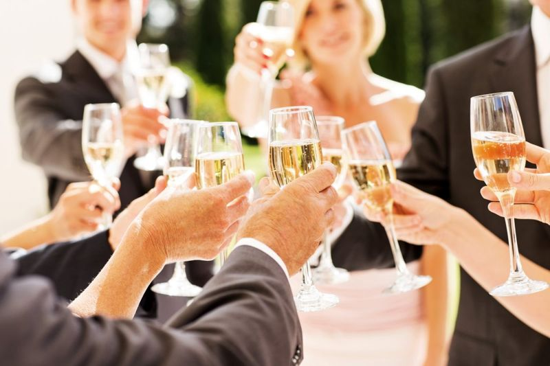 People toasting champagne at a wedding with the bride and groom