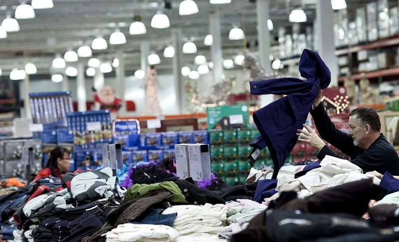 A customer looks through a pile of clothes at a Costco Wholesale Corp. store in Arlington, Virginia, U.S., on Tuesday, Nov. 9, 2010. Inventories at U.S. wholesalers climbed twice as much as forecast in September as suppliers stocked up ahead of the holiday sales season.