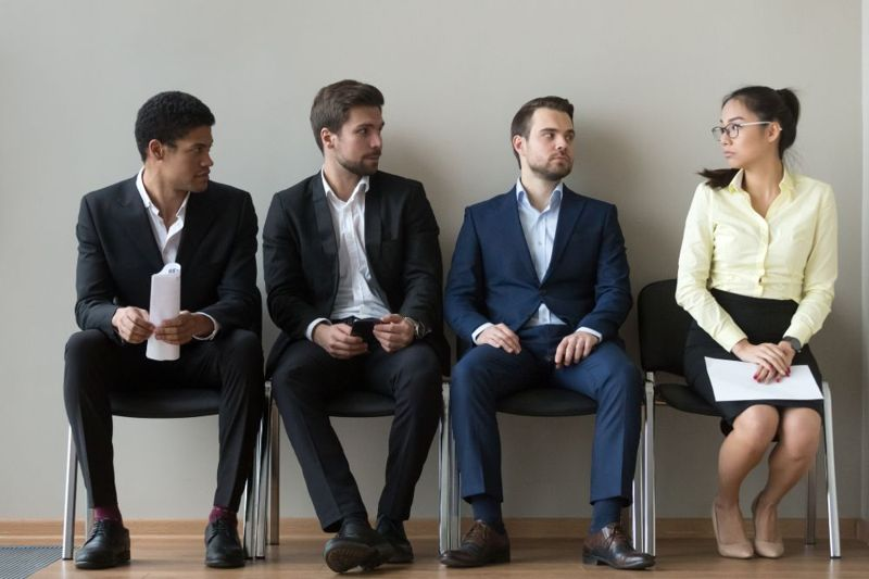 three men and one woman waiting for an interview