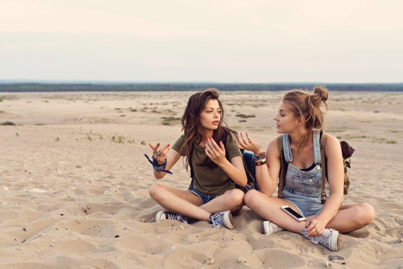Young women talking while sitting on sand. Female friends are lost in desert during hiking. They are wearing casuals.