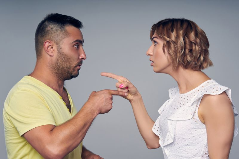 A couple man and woman pointing at each other expressing accusation isolated on gray background