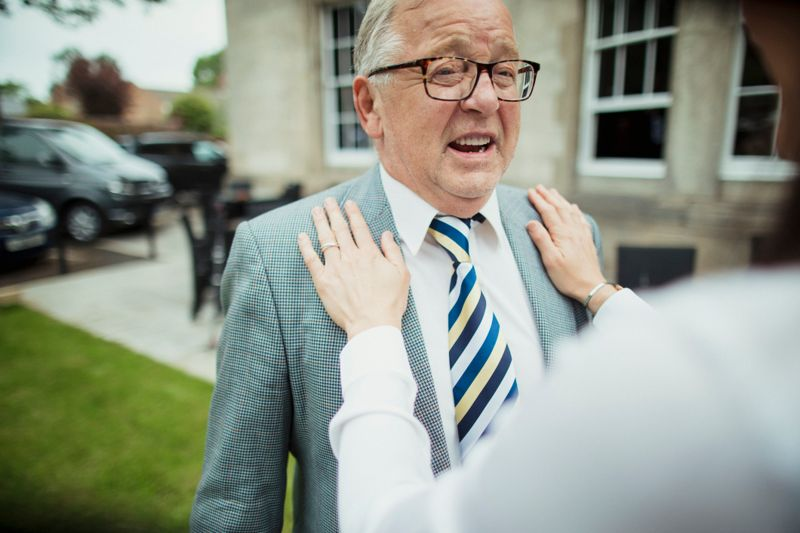 A close-up shot of a senior caucasian man getting assistance with his tie, he is wearing smart clothing and glasses.