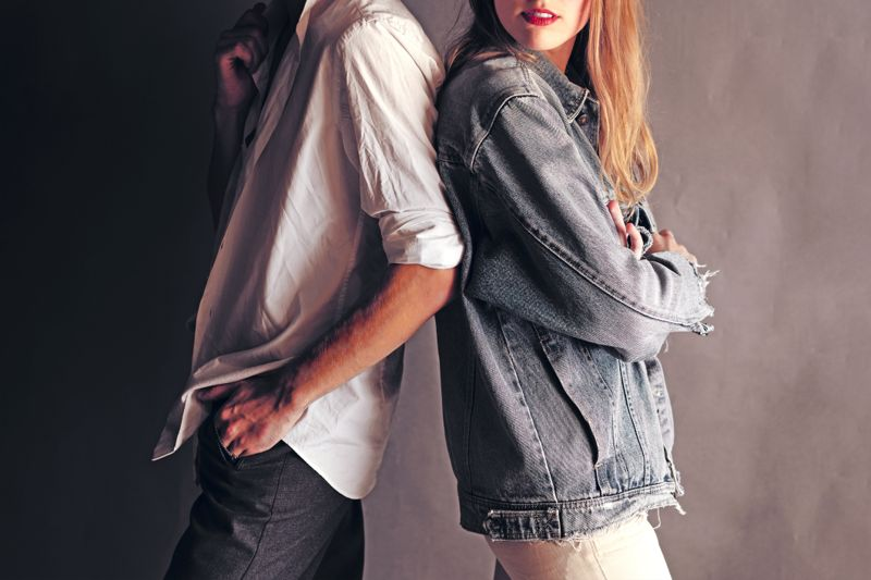 Happy Young Couple Back To Back Each Other on a Grey Wall Background. Couple ignoring each other while standing back to back