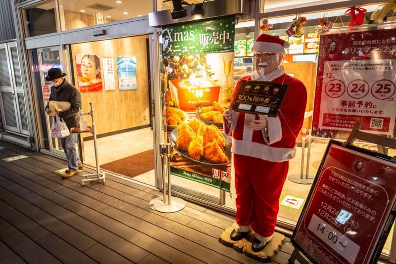 TOKYO, JAPAN - DECEMBER 23: A man holding a Christmas meal box leaves a KFC restaurant on December 23, 2020 in Tokyo, Japan. KFC at Christmas has become something of a tradition in Japan with some attributing its yuletide popularity to a kindergarten delivery being made in a Santa Claus outfit which was such a success it was requested by a number of other schools and subsequently gave the company the idea of associating its product to Christmas. The chain launched its first Christmas campaign in December 1974, and has continued to do so every year at all its outlets nationwide. In 2018, KFC Japan posted all-time high sales of roughly 68 million USD for the five days from December 21 to 25. Roughly 10 percent of its annual turnover for the entire year.