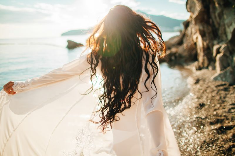 girl running dreamy with wind in hair and sunflare on beach sunset. defocus
