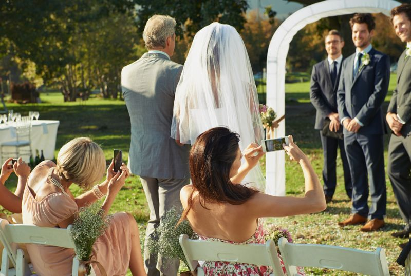Rear view shot of a father walking his daughter down the aisle while guests take photos with their cellphones