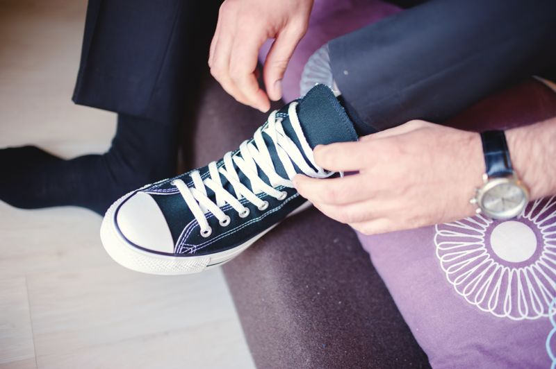 Modern hipster wedding, groom wearing sneakers instead of classic elegant shoes, tying the laces. Vintage effect on dressing event