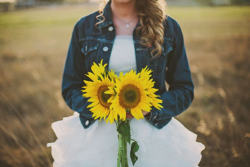 Bride in jeans jacket with sunflower bouquet staying in the field on golden hour.