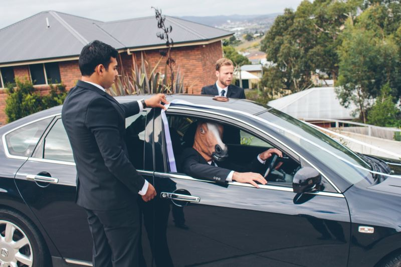 Groom and Groomsman getting car ready for wedding while driver has fun wearing a horse mask