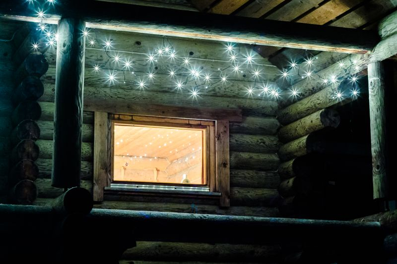 The outdoor sauna building is decorated with tiny lamp lights during the Christmas time.