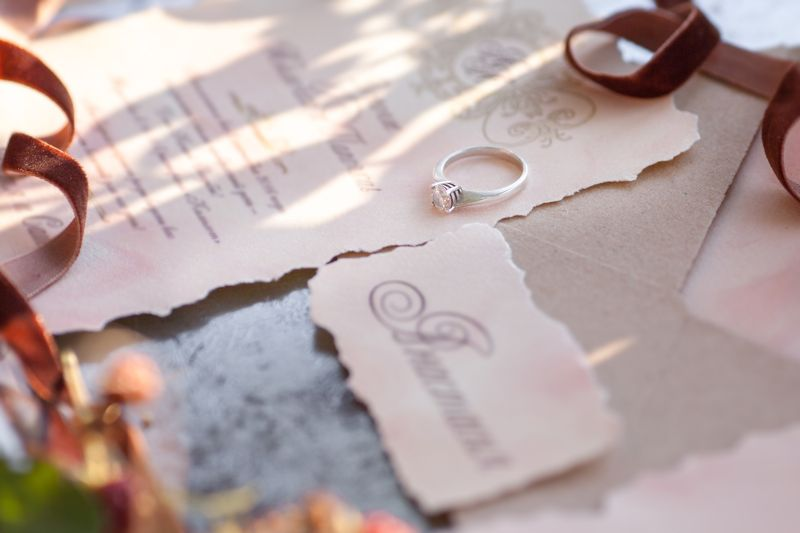 wedding ring lies on the invitation. Golden ring with diamond