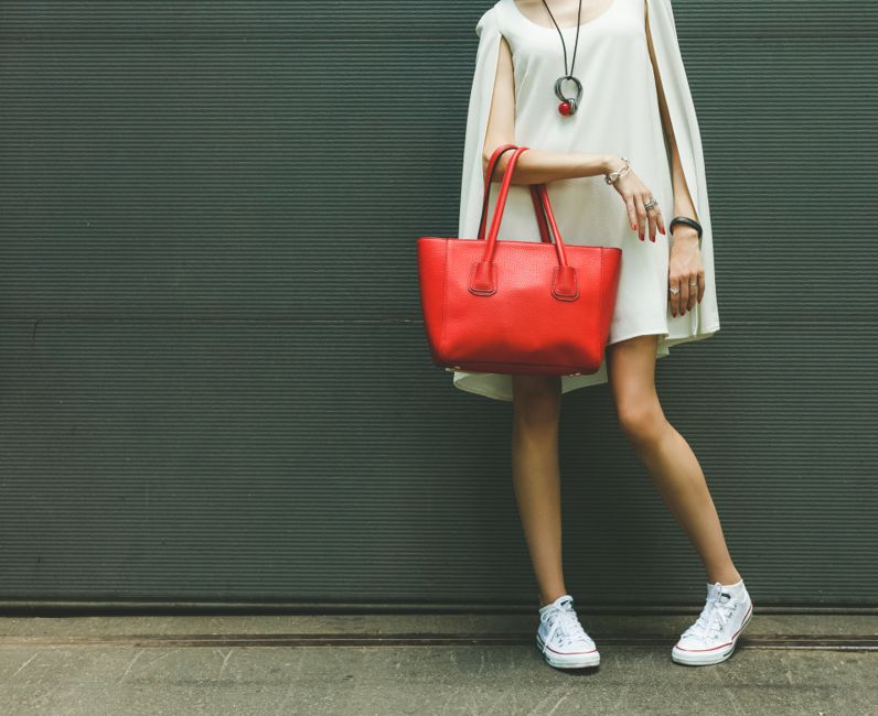 Fashionable beautiful big red handbag on the arm of the girl in a fashionable white dress and sneakers, posing near the wall on a warm summer night. Warm color.