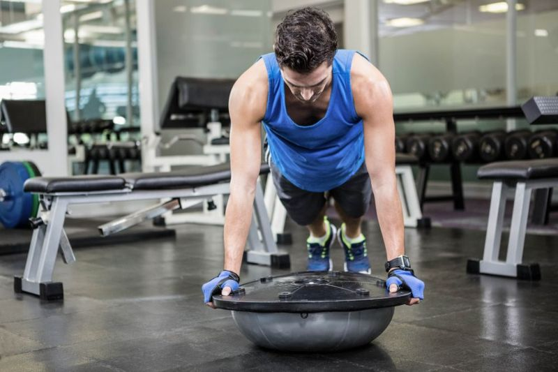 man doing a push up or burpee with bosu ball