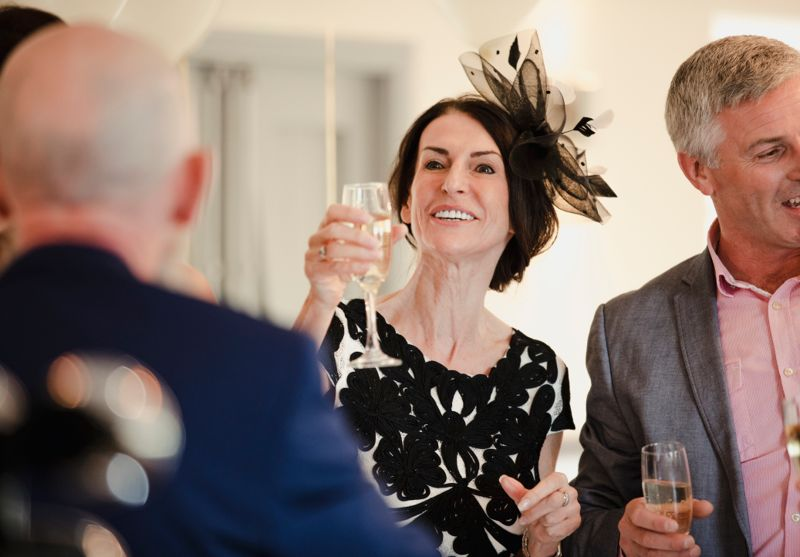 Bride's parents are toasting to their daughter and son-in-law on their wedding day. They are raising their glasses of champagne.