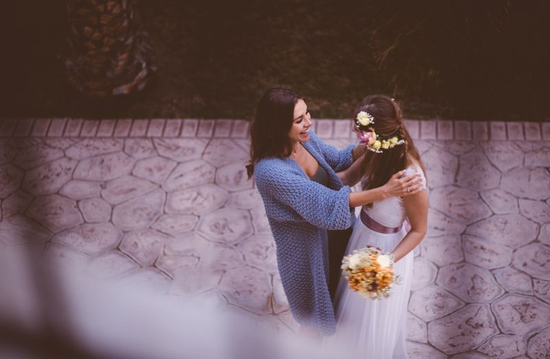 Happy woman guest embracing and congratulation beautiful bride at rustic cottage wedding in Europe