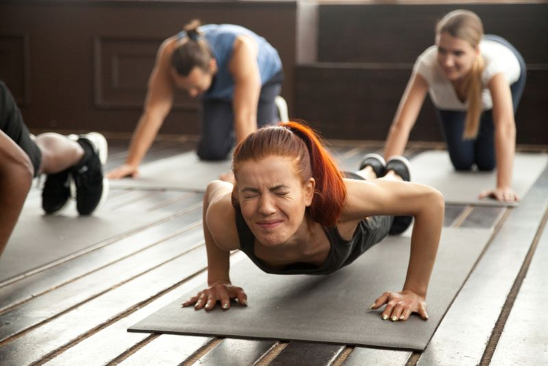 young woman struggling in fitness class