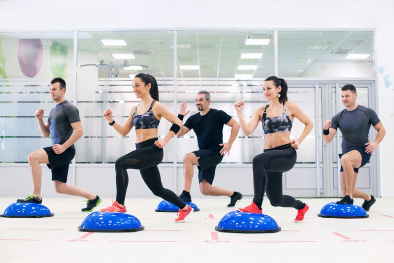 group of people doing split squats or lunges on bosu balls