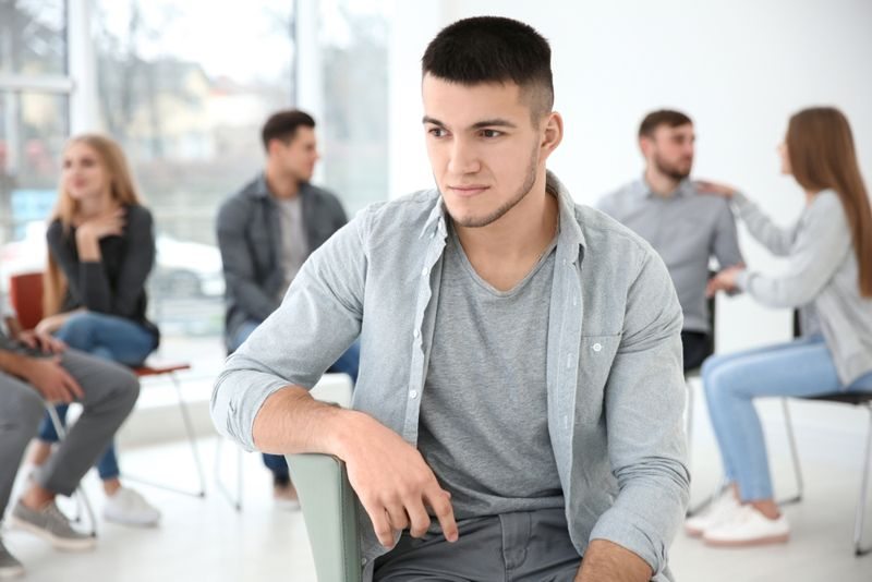man with social anxiety sitting outside group