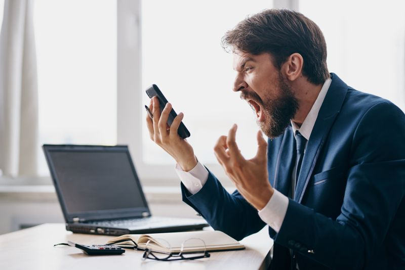 angry businessman yelling into his phone