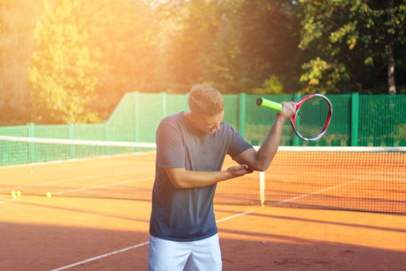 man holding sore elbow after tennis