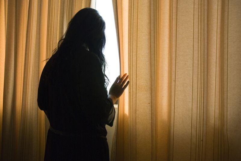 agorophobia concept woman peeking out window