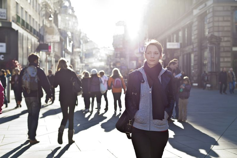 woman walking on busy street, people behind her