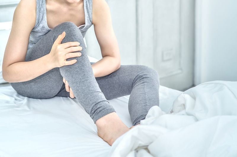 woman in bed in morning with sore leg