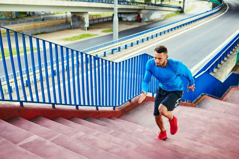 man running intervals on outdoor stairs