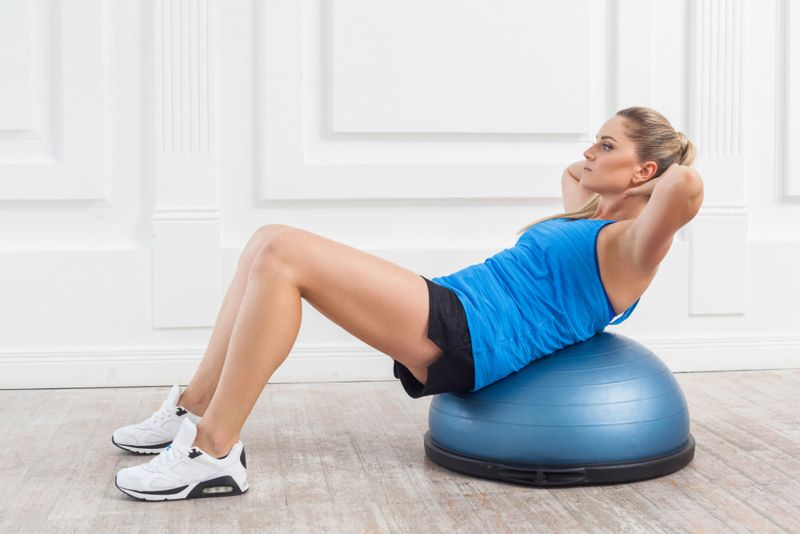 woman doing a sit up or crunch on a bosu ball