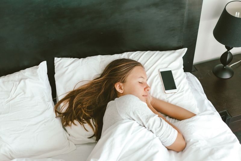 young girl sleeping with her phone beside her