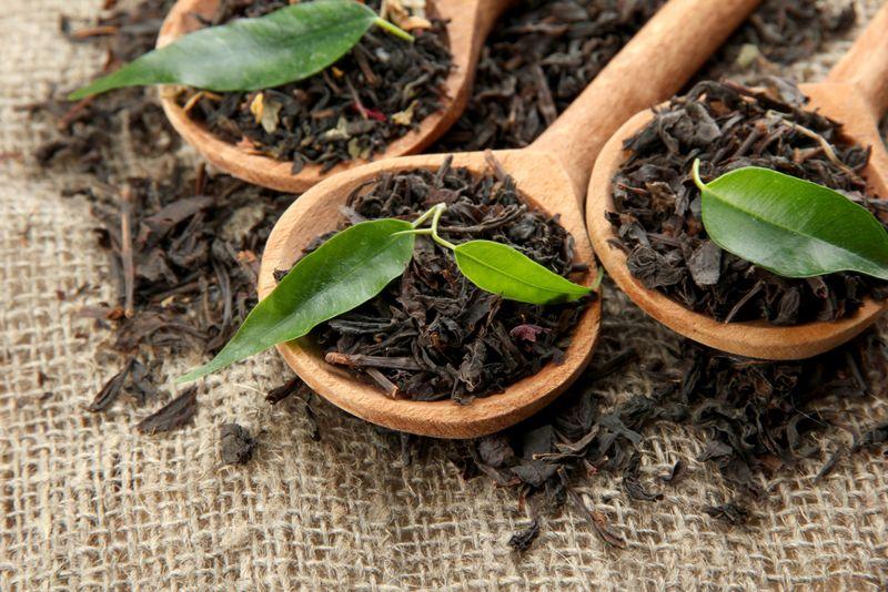 ceylon tea leaves in wooden scoops