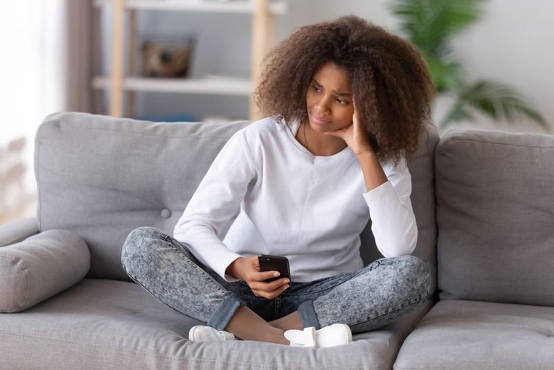 young woman on couch with phone is upset