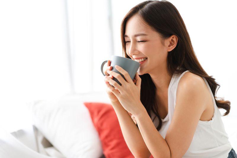smiling alert woman drinking tea