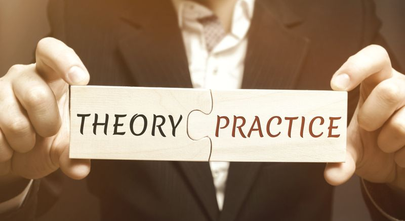 man holding puzzle pieces that say theory and practice
