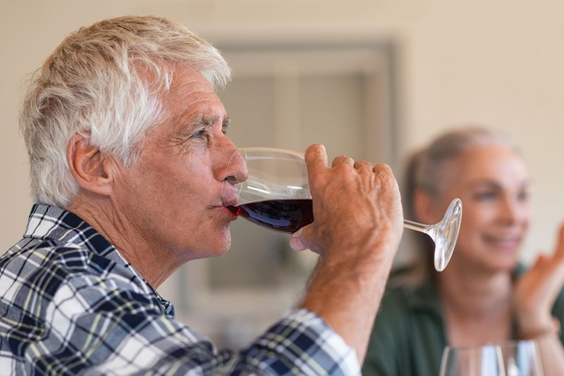 older man having a glass of red wine