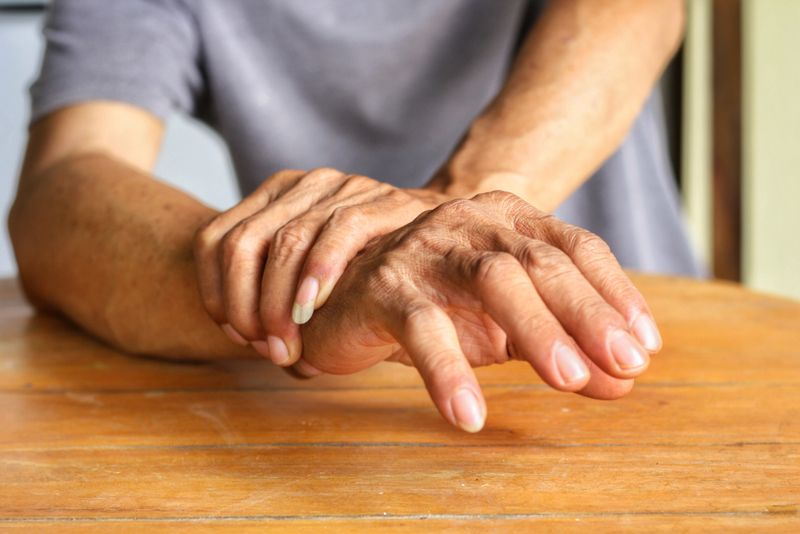older man with hand tremors