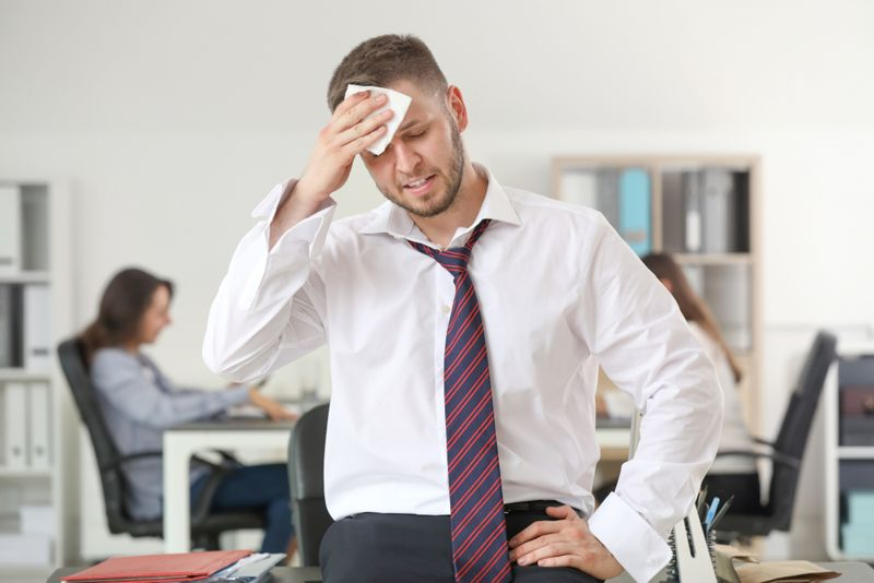 nervous sweating man in office