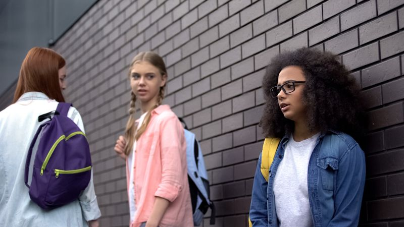 young women insulting another classmate