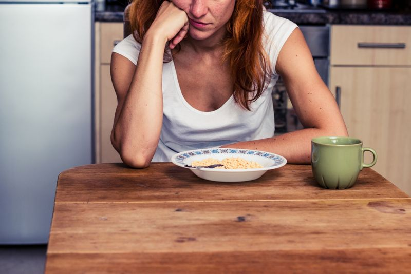 woman looking unhappy with bowl of food