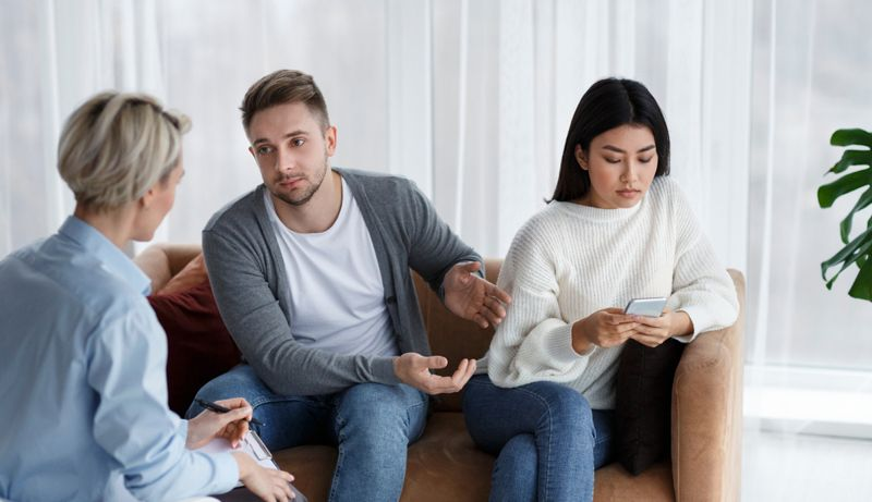 couple at therapist with woman on her phone