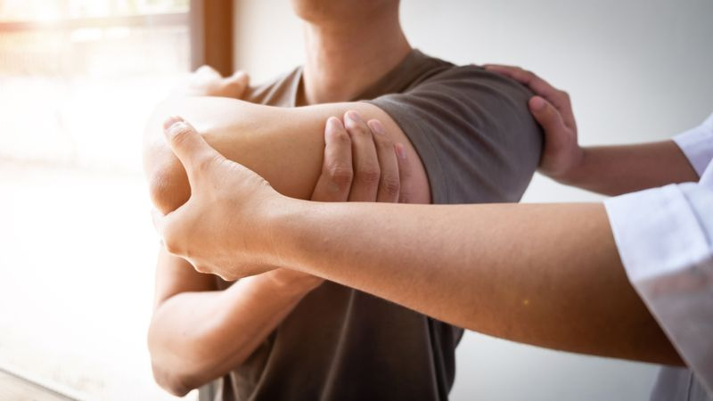 physical therapist helping work client's shoulder