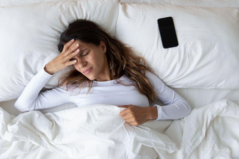 woman in bed beside phone has headache
