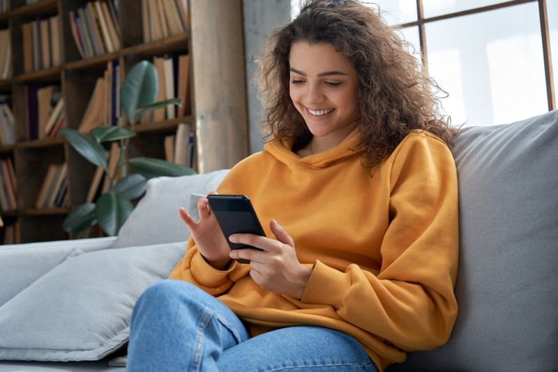 smiling young woman scrolling through phone
