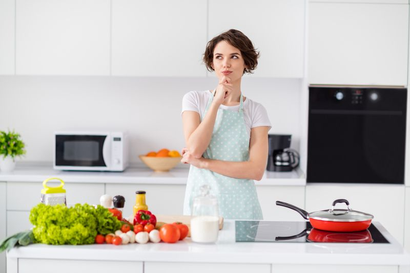 woman in kitchen thinking about what to make for dinner