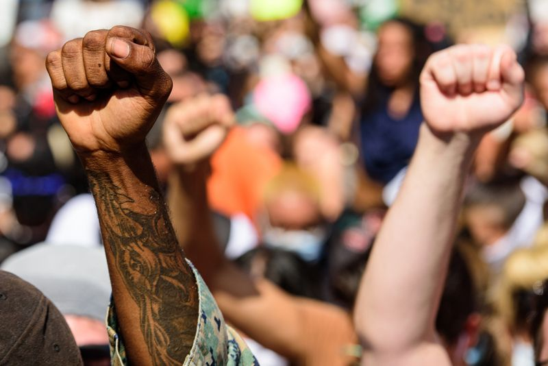 man's black arm and a white arm raised in protest